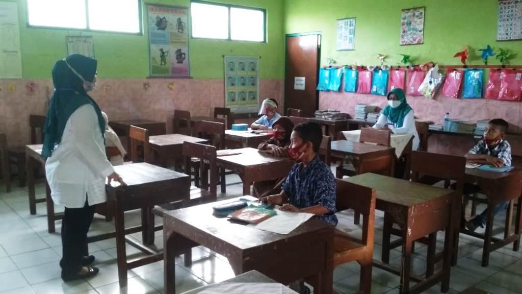 BERJARAK: Siswa-siswi SD 4 Cendono menjaga jarak saat hadir ke sekolah. (NISA HAFIZHOTUS SYARIFA/LINGKAR JATENG)