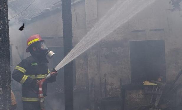 BERJIBAKU: Petugas Damkar Satpol PP Sukoharjo berupaya menjinakkan api yang membakar rumah Tuminah, Jumat (26/12/2020). (PUJOKO/LINGKAR.CO)