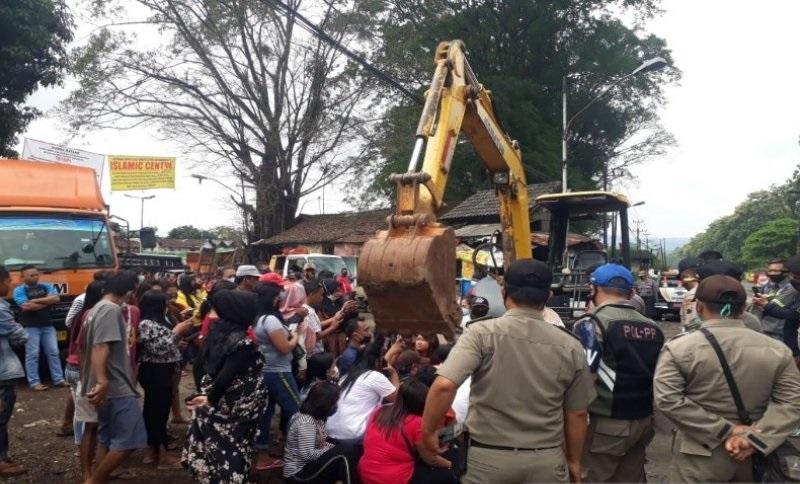 Para penghuni pangkalan truk di Desa Petamanan, Kecamatan Banyuputih, Kabupaten Batang melakukan aksi menghalangi alat berat yang akan mengeruk tanah di pintu masuk pangkalan truk, Selasa (29/12). (ANTARA/LINGKAR.CO)
