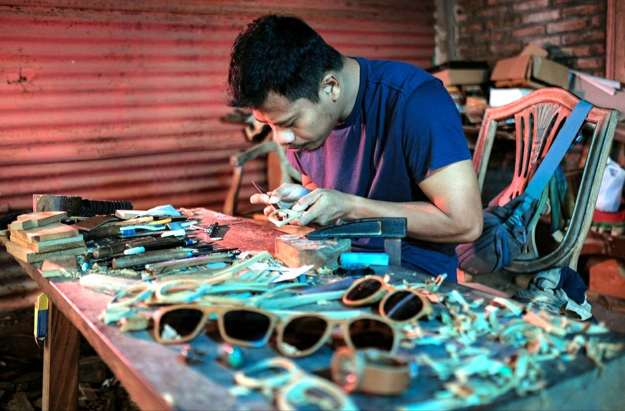 Salah satu warga Jepara tengah membuat kerajinan ukir berupa kacamata kayu, belum lama ini. (MIFTAHUL UMAM/LINGKAR.CO)