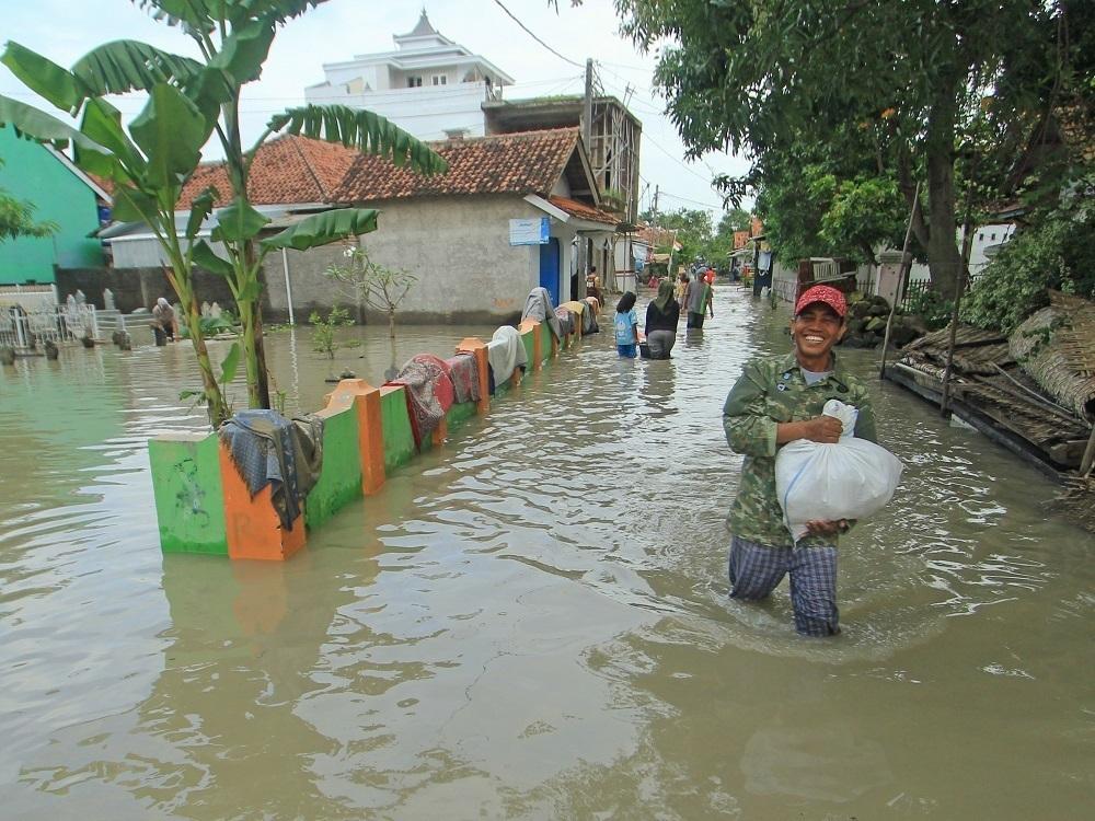 Warga berjalan menerobos banjir yang merendam Desa Suranenggala Lor, Kecamatan Suranenggala, Kabupaten Cirebon, Jawa Barat, Selasa (19/1). (ANTARA FOTO/LINGKAR.CO)