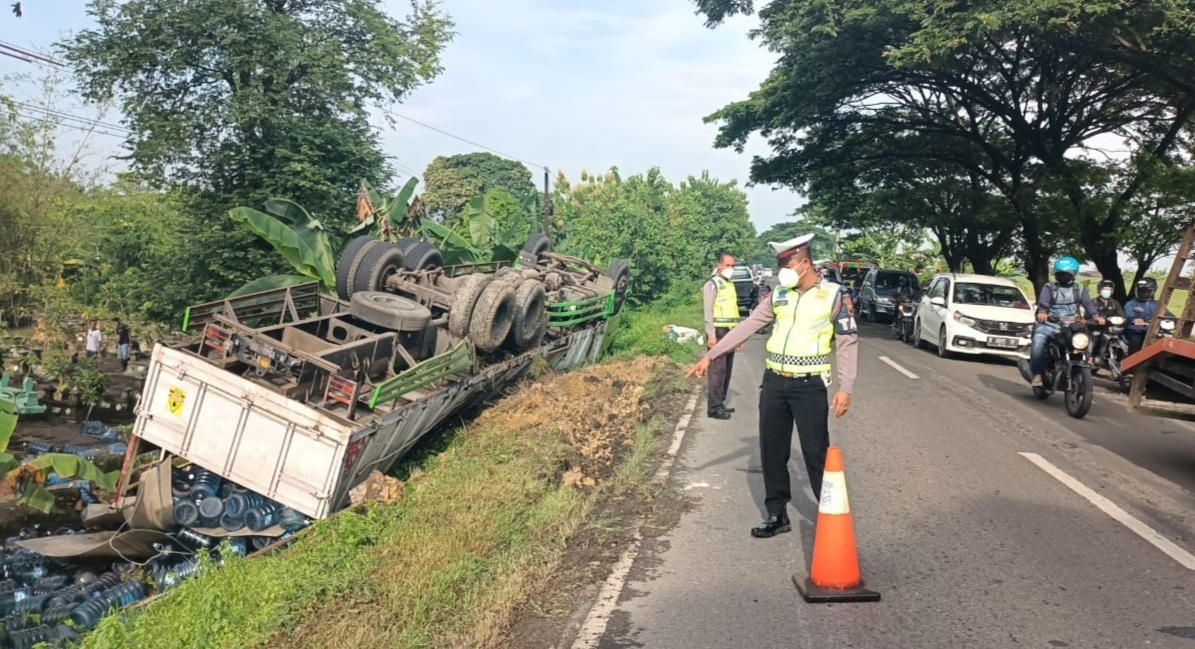 Kondisi truk yang mengalami terguling di depan area pemakaman Desa Jatilor, Senin (18/1). (ANSORI/LINGKAR.CO)