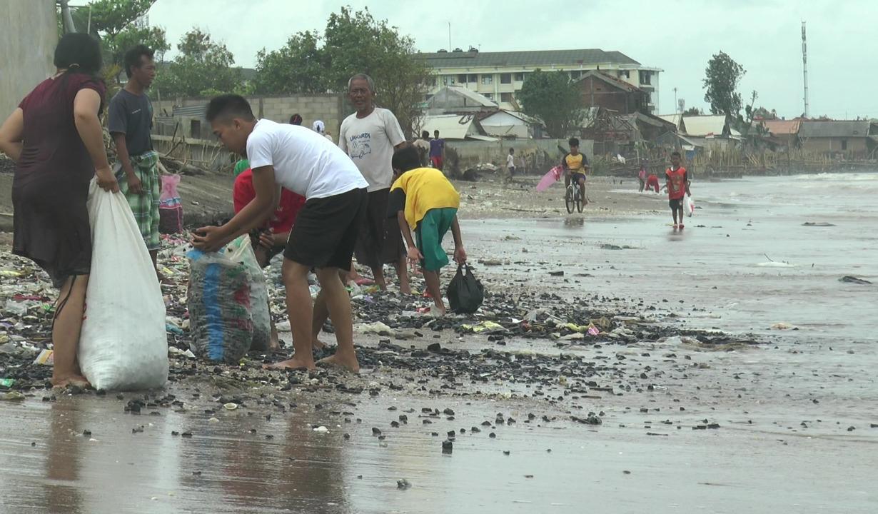 Sejumlah warga tampak mengumpulkan batu bara yang tercecer di Pantai Sekembu, Jum'at (15/1). (MIFTAHUL UMAM/LINGKAR.CO)