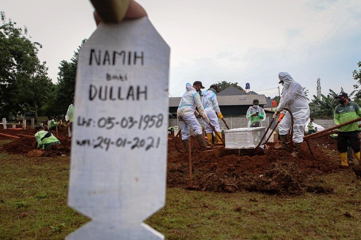 Petugas memakamkan jenazah COVID-19 di TPU Bambu Apus, Jakarta, Minggu (24/1). (KORAN LINGKAR JATENG/LINGKAR.CO)