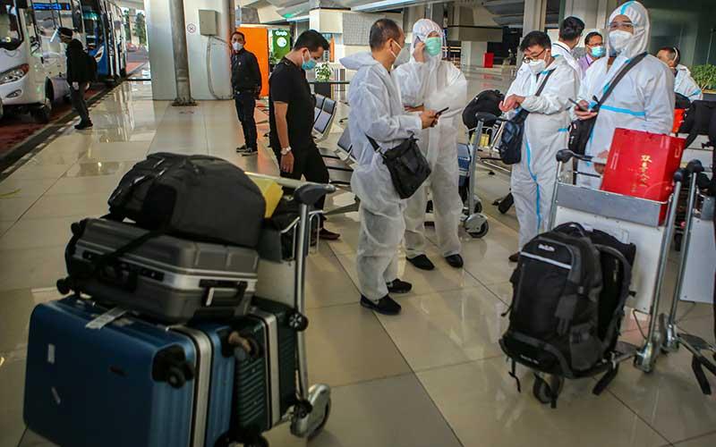 Sejumlah warga negara asing (WNA) dengan menggunakan baju hazmat tiba di Bandara Internasional Soekarno Hatta, Tangerang, Banten, Sabtu (2/1). (ANTARA FOTO/LINGKAR.CO)