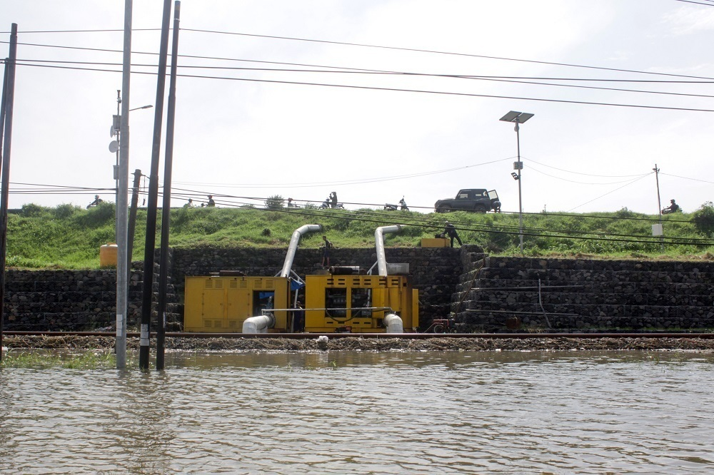 Pekerja berada di sekitar mesin pompa khusus penyedot banjir yang terletak di pinggir tanggul penahan Lapindo, Porong Sidoarjo, Jawa Timur, Senin (18/1). (ANTARA/LINGKAR.CO)