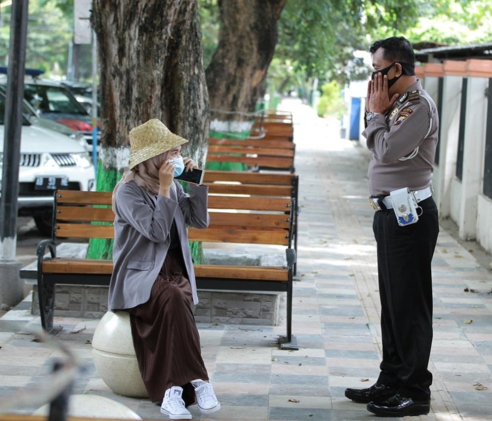 Petugas kepolisian meminta warga untuk mengenakan masker.(DOK. LINGKAR.CO)