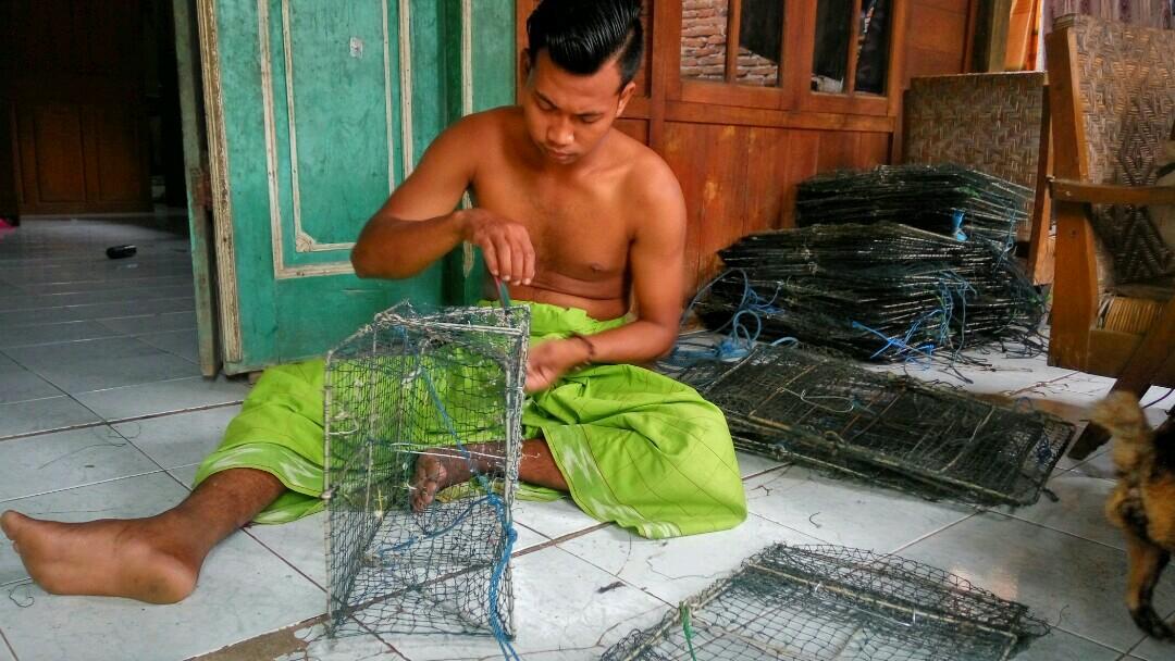 Seorang nelayan rajungan saat memperbaiki bobo (alat tangkap rajungan) baru-baru ini. (MIFTAHUS SALAM/LINGKAR.CO)