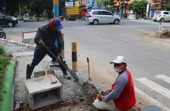 Para pekerja sedang mengerjakan memasang keramik di drainase dan trotoar Jalan Wachid Hasyim baru-baru ini. (FARIDHA NADHIRA/LINGKAR JATENG)