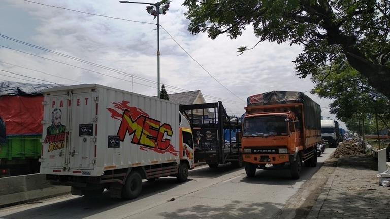 PERLAHAN: Pemberlakuan contra flow pada lalu lintas Demak-Semarang dikarenakan kemacetan yang disebabkan banjir dan jalan berlubang, Selasa (9/2/2021).(ADITIA ARDIAN/KORAN LINGKAR JATENG)