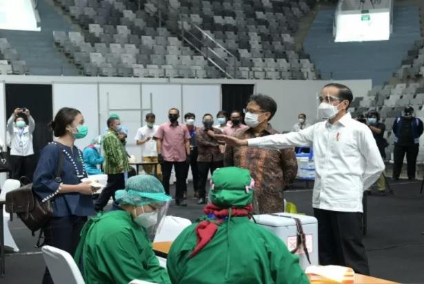Presiden Joko Widodo (kanan) didampingi Menteri Kesehatan Budi Gunadi Sadikin meninjau pelaksanaan Vaksinasi Massal bagi tenaga kesehatan dosis pertama vaksin COVID-19 Sinovac di Istora Senayan, Jakarta, Kamis (4/2/2021). (ANTARA/KORAN LINGKAR JATENG)