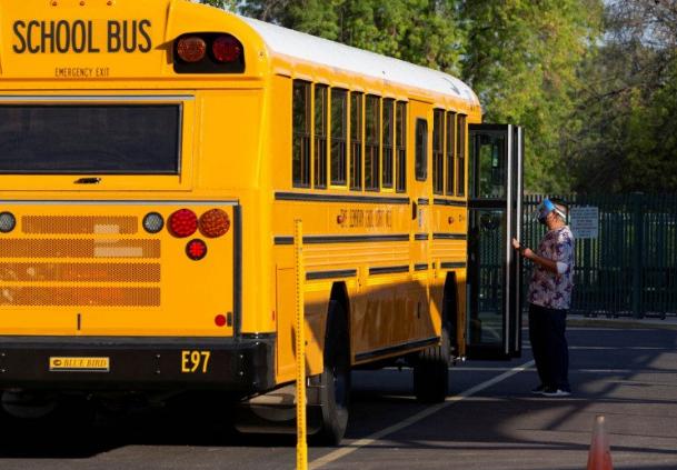 Seorang pegawai menunggu untuk membantu para pelajar turun dari bus di Sekolah Dasar Rover di Tempe, Arizona, Amerika Serikat, Senin (17/8/2020). (ANTARA/LINGKAR JATENG)