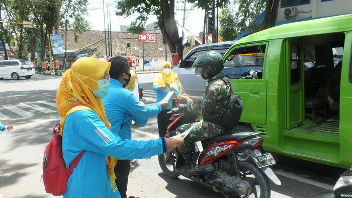 KAMPANYE: Anggota Yayasan Mentari Sehat Indonesia Kabupaten Grobogan membagikan brosur imbauan penecegahan penyakit TBC di Jalan Suprapto. Senin (29/3). (MUHAMAD ANSORI/LINGKAR.CO)