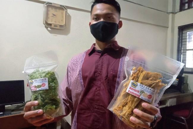 Catur Prasetyo, siswa kelas XI TKR I SMKN Jenawi memperlihatkan produk keripik pelepah pisang, Kamis (4/3/2021). (PUJOKO/LINGKAR.CO)