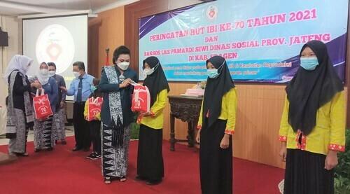 BERIKAN: Ketua Ikatan Bidan Indonesia (IBI) kabupaten sragen Ny Damai Tatag Prabawanto saat menyerahkan bantuan kepada anak, Kamis (25/6). (ISTIMEWA/LINGKAR.CO)