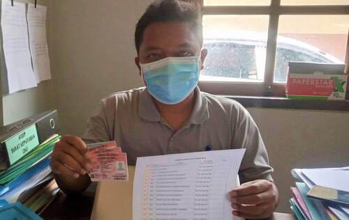 MENUNJUKKAN: PLT Carik Trangkil Adi Priyo sedang menunjukkan KIA beserta daftar penerima KIA yang ada di Desa Trangkil Kemarin. (IBNU MUNTAHA/LINGKAR.CO)