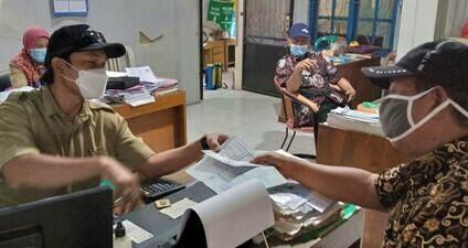 TERTIB: Warga sedang menyerahkan berkas penunjang untuk mengajukan surat pengantar di Kantor Desa Jatimulyo, Kecamatan Wedarijaksa kemarin, Senin (12/7/21). (IBNU MUNTAHA/LINGKAR.CO)