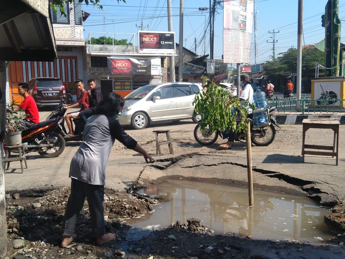 MENUNJUKKAN: Seorang warga menunjukkan lokasi semburan air dan lumpur yang ada di Kecamatan Wedarijaksa, Kabupaten Pati, Sabtu (24/7/21). (MIFTAHUS SALAM/LINGKAR.CO)