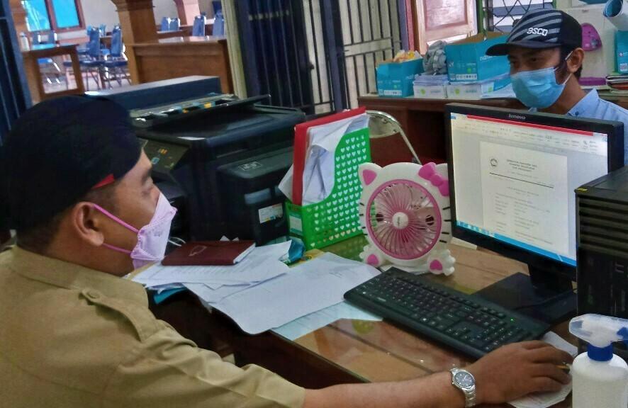 ADMINISTRASI: Warga Desa Bangsalrejo, Kecamatan Wedarijaksa sedang melakukan permohonan surat pengantar untuk mengurus berkas kependudukan kemarin, Senin (12/7/21). (IBNU MUNTAHA/LINGKAR.CO)
