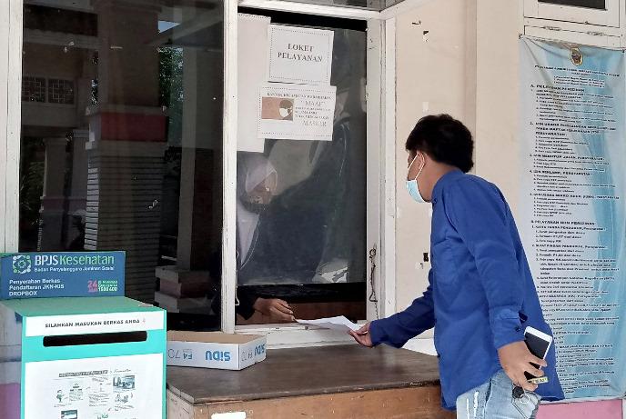TERTIB: Masyarakat Kecamatan Wedarijaksa sedang menyerahkan berkas penunjang untuk mengajukan permohonan berkas kepada petugas kemarin, Senin (13/7/21). (IBNU MUNTAHA/LINGKAR.CO)