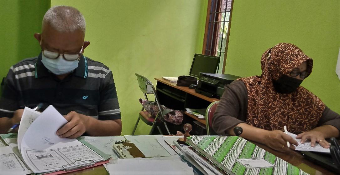 PERIKSA: Kepala Desa Kutoharjo, Kecamatan Pati Hartono (kirim) sedang menandatangi berkas permohonan kependudukan yang diajukan masyarakat belum lama ini. (IBNU MUNTAHA/LINGKAR.CO)