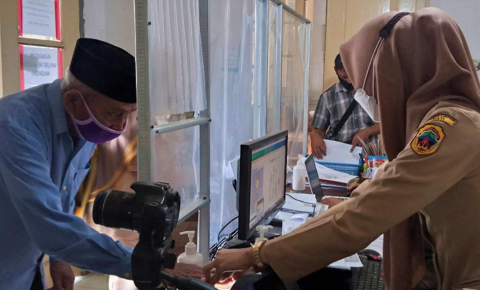 PROSEDUR: Petugas sedang melakukan perekaman data biometrik warga yang melakukan perekaman data di Kantor Kecamatan Juwana kemarin, Senin (14/7/21). (IBNU MUNTAHA/LINGKAR.CO)