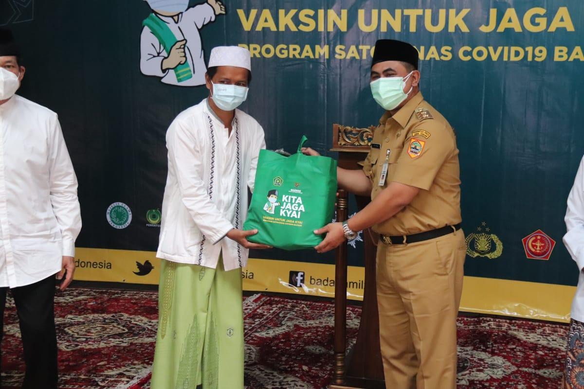 PENYERAHAN: Wagub Jateng, Taj Yasin Maimoen, saat menyerahkan paket imun secara simbolis saat menghadiri vaksinasi kalangan Ponpes Al-Ishlah, Mangkang, Kota Semarang, Senin (2/8/2021). (REZANDA AKBAR D/LINGKARJATENG.CO.ID)