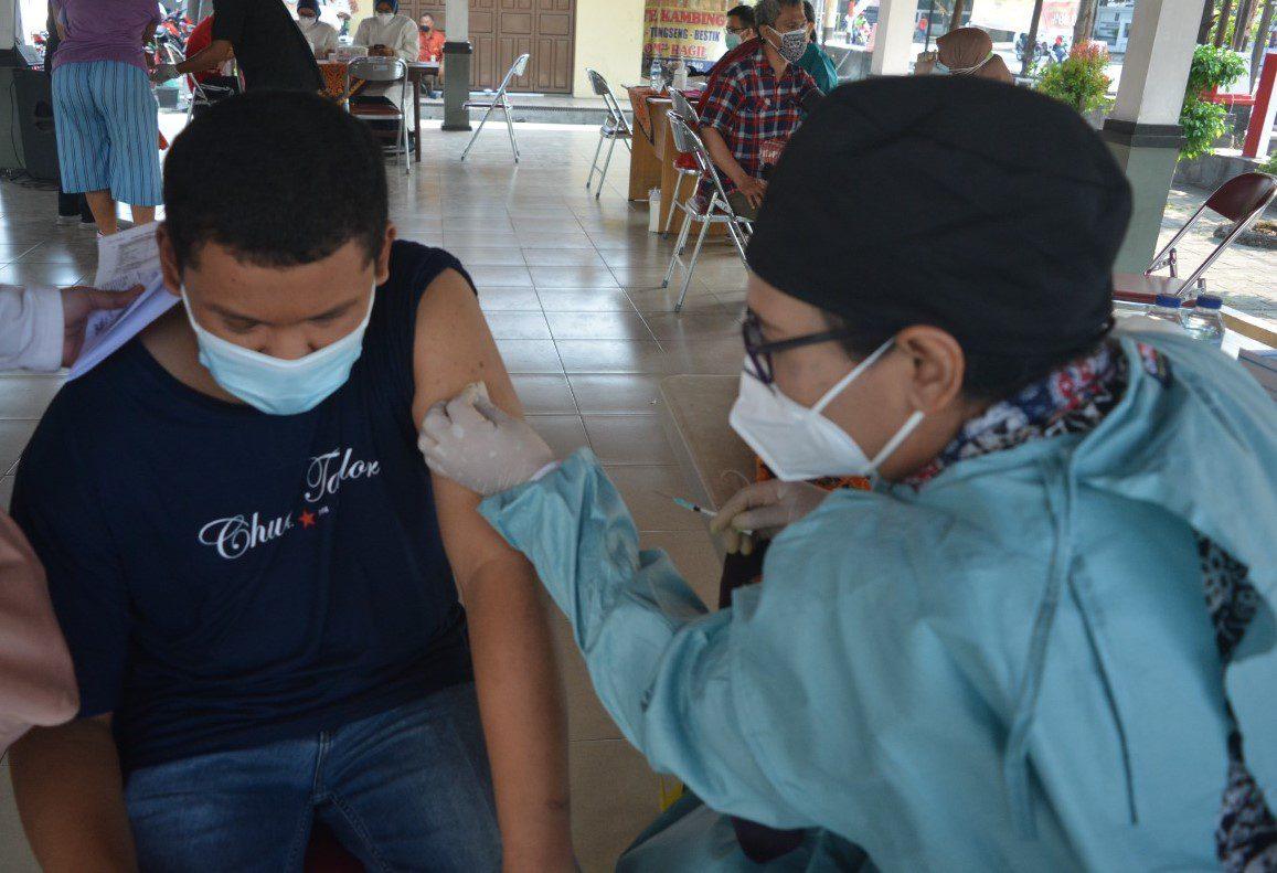 TERIMA: Seorang difabel menerima vaksin Covid-19 dosis pertama, Selasa (10/8/2021) di Taman Sobokartti, Kebonagung, Kecamatan Semarang Timur. (DINDA RAHMASARI/LINGKAR.CO)
