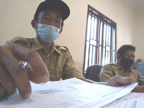 TELITI: Perangkat Desa Mojoagung, Kecamatan Trangkil sedang memperhatikan data kependudukan. (IBNU MUNTAHA/LINGKAR.CO)