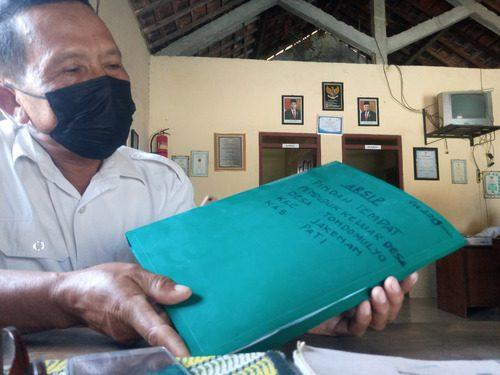 ILUSTRASI: Perangkat Desa Tondomulyo, Kecamatan Jakenan sedang menunjukkan berkas pencatatan pindah tempat warga. (IBNU MUNTAHA/LINGKAR.CO)