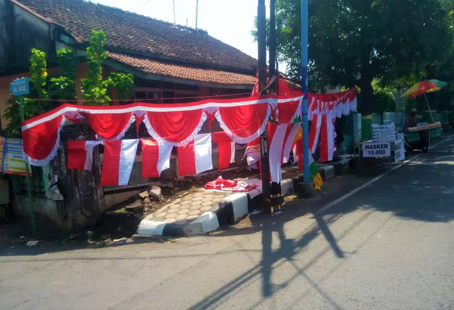 MENJAJAKAN: Penjual bendera tampak sepi pembeli. (NAILUL MUTTALIBIN KORAN LINGKAR JATENG/LINGKAR.CO)