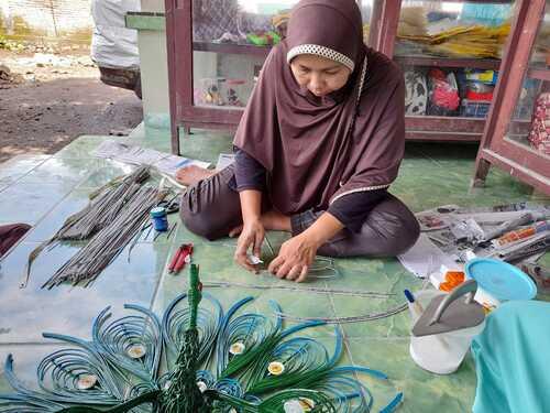 Menyulam: Pembuatan burung merak dari koran bekas yang digulung. (ISTIMEWA/LINGKAR.CO)
