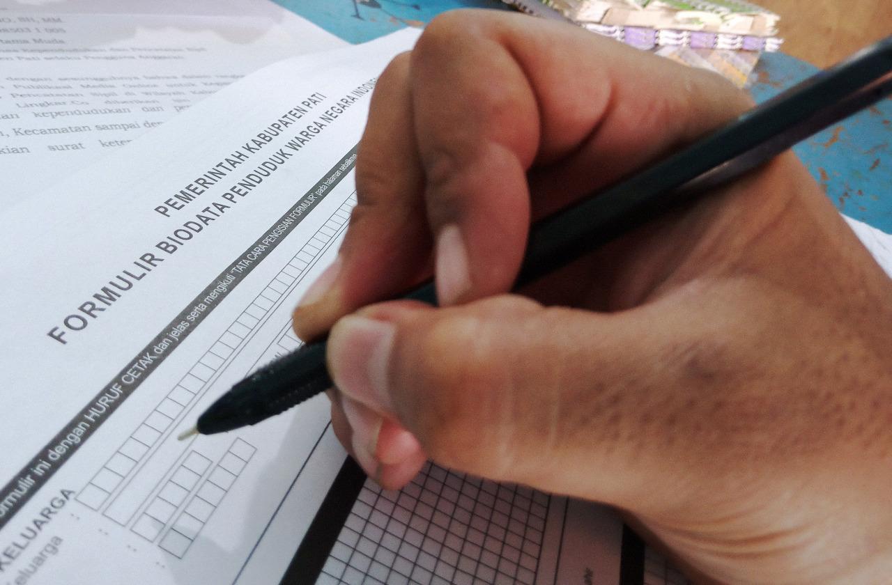 ILUSTRASI: Pencocokan data kependudukan dengan cara manual. (IBNU MUNTAHA/LINGKAR.CO)