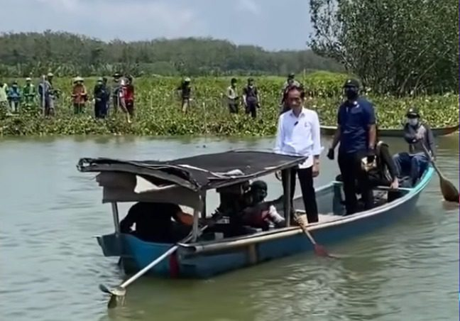 Presiden Jokowi, menaiki perahu untuk menyapa warga yang berada di seberang sungai, di Desa Tritih Lor, Kecamatan Jeruklegi, Kabupaten Cilacap, Jateng, Kamis (23/9/2021) pagi. FOTO: Tangkap layar Youtube Setpres/Lingkar.co