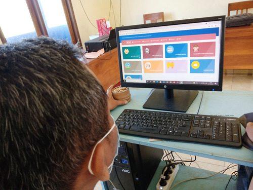 ILUSTRASI: Perangkat Desa Jontro, Kecamatan Wedarijaksa sedang menunjukkan situs pelayanan berkas kependudukan Disdukcapil Pati. (IBNU MUNTAHA/LINGKAR.CO)