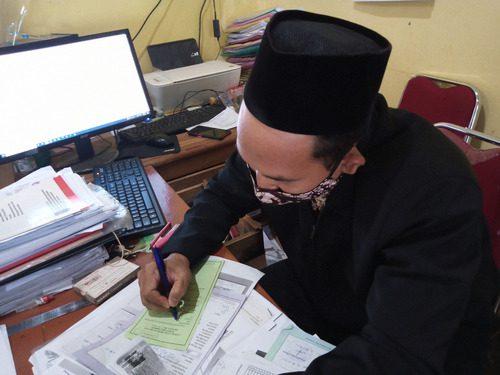 TULIS: Perangkat Desa Tanjungrejo, Kecamatan Margoyoso sedang mempersiapkan permohonan berkas kependudukan warga setempat sebelum mengirimnya melalui jasa kurir. (IBNU MUNTAHA/LINGKAR.CO)