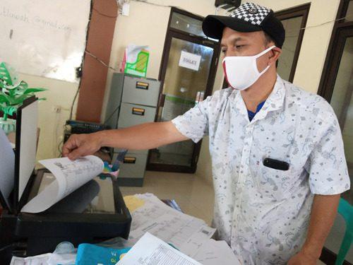 GANDA: Kasi Pemerintahan Desa Tluwah, Kecamatan Juwana sedang melakukan fotokopi KK pada kantor kepala desa setempat belum lama ini. (IBNU MUNTAHA/LINGKAR.CO)