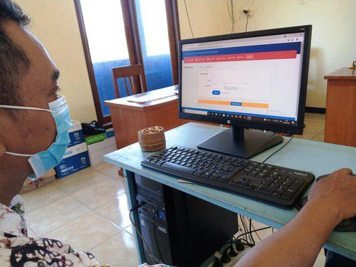 PERMOHONAN: Perangkat Desa Jontro, sedang melakukan pengajuan permohonan berkas kependudukan secara daring melalui situs pelayanan Disdukcapil Pati pada kantor kepala desa setempat kemarin. (IBNU MUNTAHA/LINGKAR.CO)
