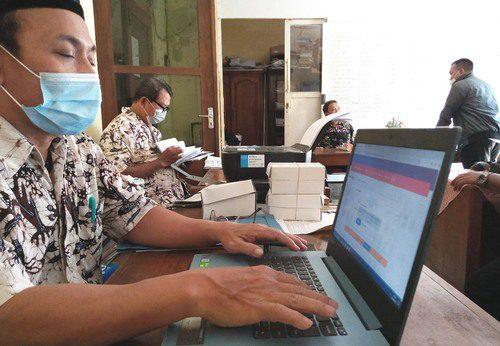 ILUSTRASI: Perangkat Desa Ngurensiti, Kecamatan Wedarijaksa sedang melihat status permohonan melalui situs Disdukcapil Pati secara daring belum lama ini. (IBNU MUNTAHA/LINGKAR.CO)