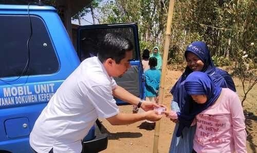 ILUSTRASI: Petugas pelayanan Disdukcapil sedang memberikan KIA pada pemohon. (ISTIMEWA/LINGKAR.CO)