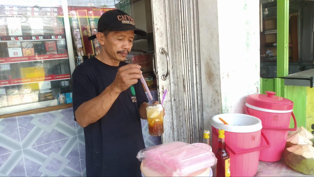 Penjual kelapa muda, Martono sedang melayani pembeli. FOTO: DANANG DISKA ATMAJA/Lingkar.co
