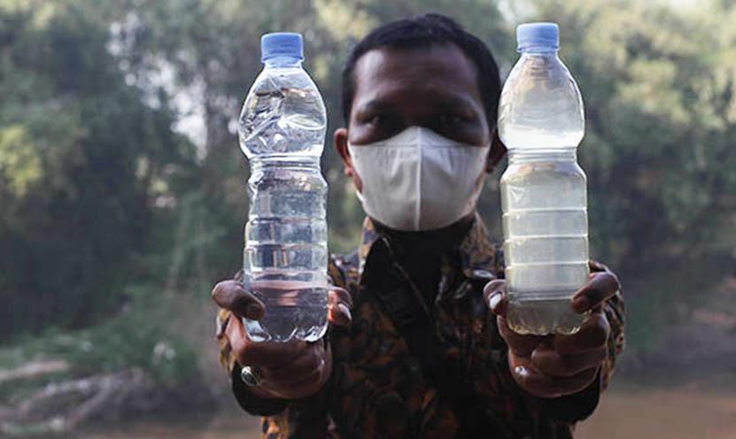 Perumda Air Minum Toya Wening Solo menunjukkan sampel air baku yang sudah tercemar limbah alkohol dan yang belum tercemar di bantaran Sungai Bengawan Solo, Nusupan, Kadokan, Grogol, Sukoharjo, Selasa (7/9/2021). Sumber : wartawan Solopos.com