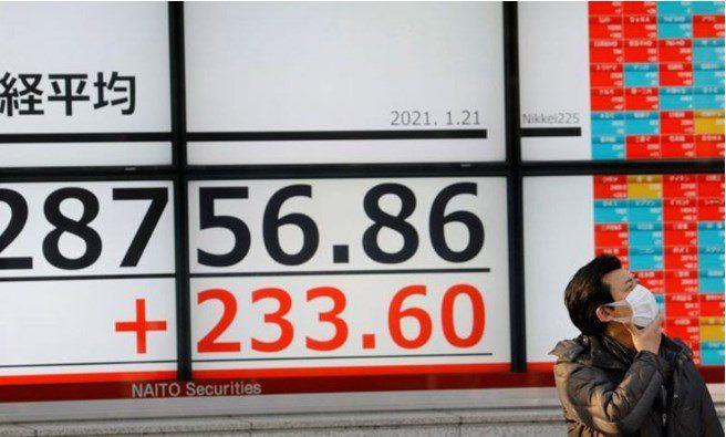 Ilustrasi: Seorang pria yang mengenakan masker pelindung, di tengah wabah penyakit virus corona (COVID-19), berdiri di depan sebuah papan elektonik yang menunjukkan indeks saham Nikkei di luar sebuah perusahaan pialang di Tokyo, Jepang . IST/LINGKAR.CO