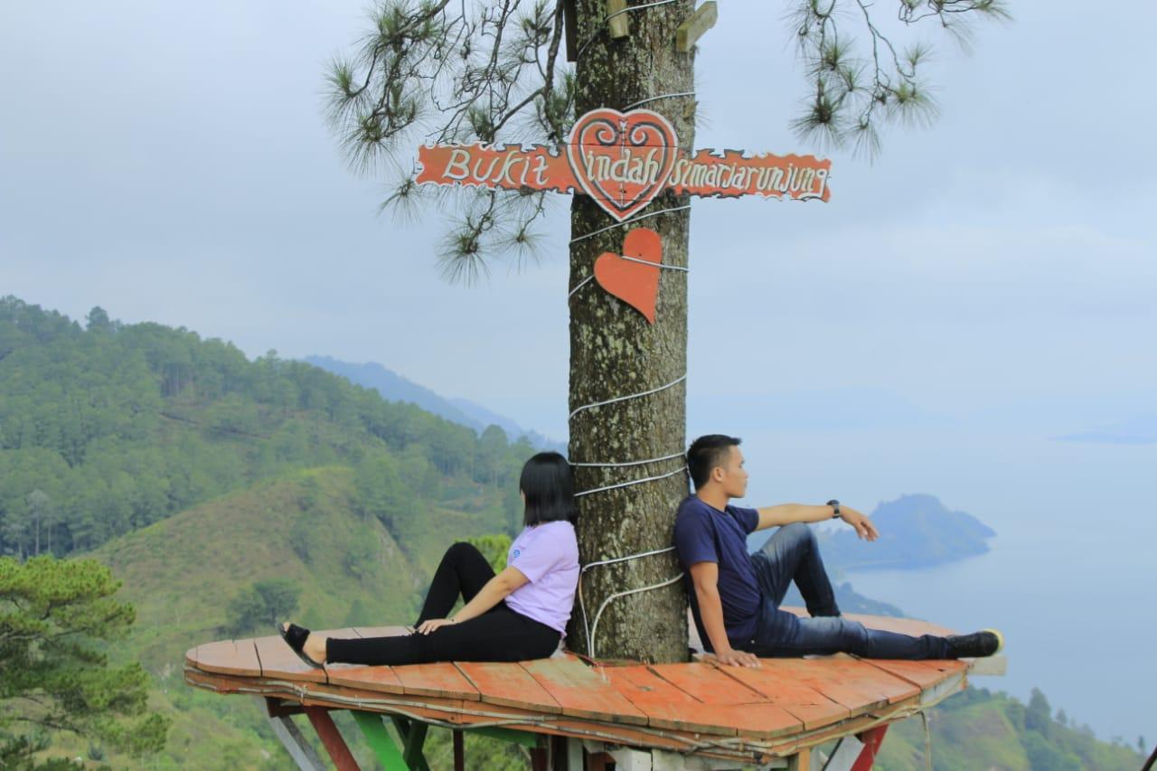 Sepasang kekasih melakukan foto bersama di Wisata Bukit Indah Simarjarunjung, Jumat (1/10/2021). FOTO: Istimewa/Lingkar.co